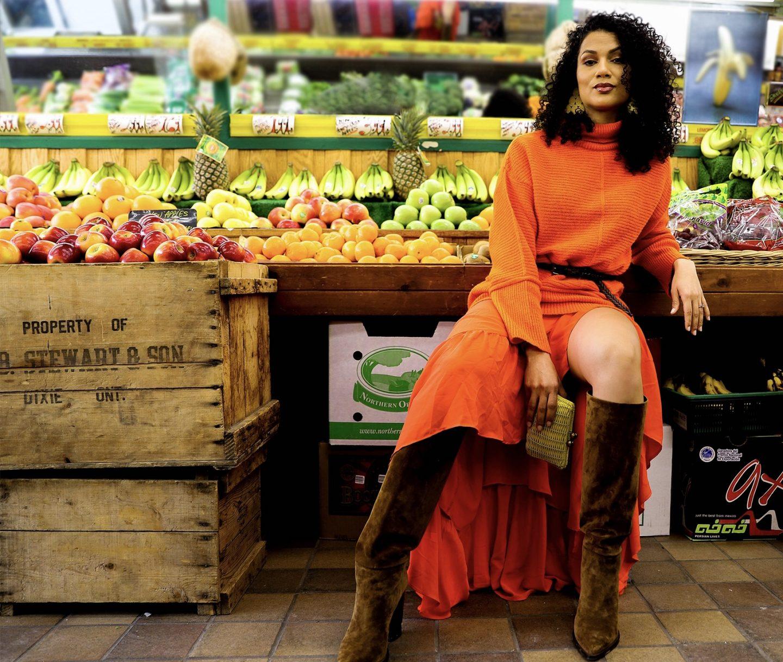 girl in orange sweater and skirt in fruit mart