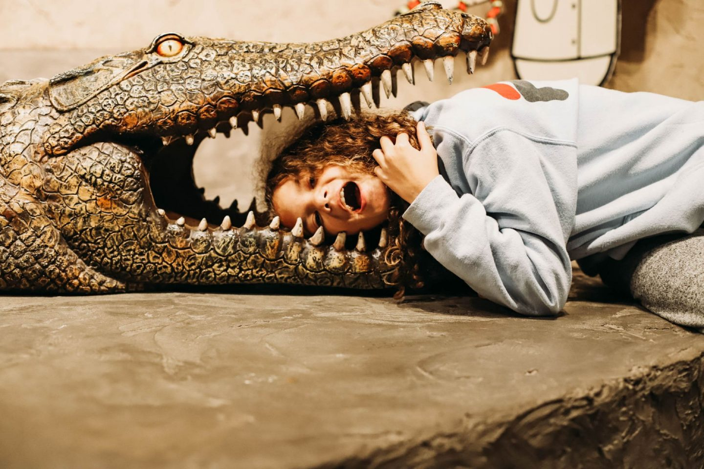 girl with her head on a crocodile's mouth at Reptilia Zoo