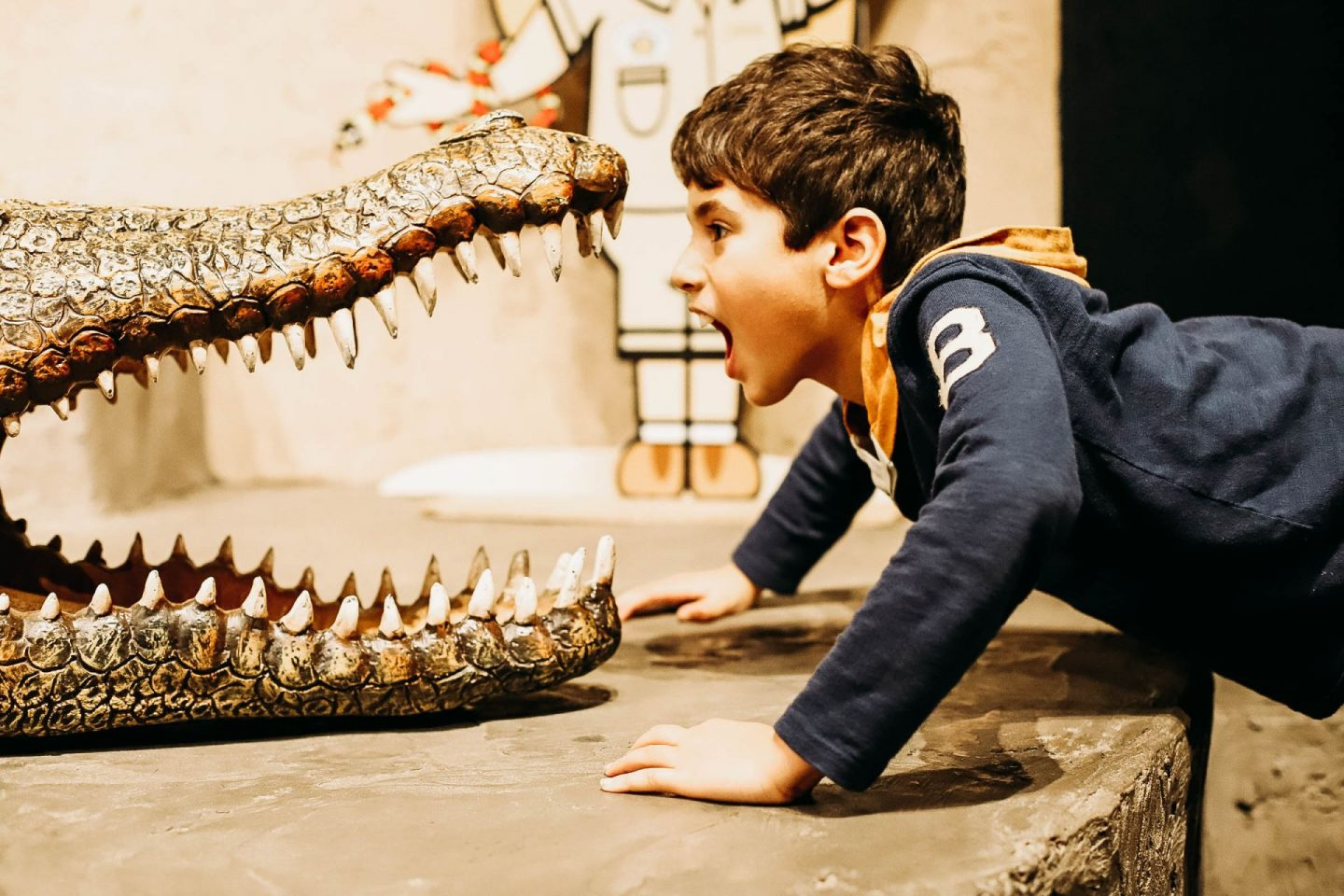 a boy looking into the face of a crocodile